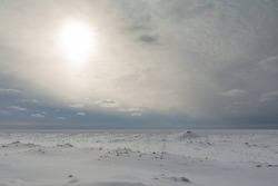 A pale winter sky rests above a still and silent frozen landscape on Lake Huron