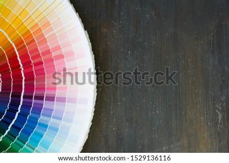 A palette of different colors and shades on a dark wooden background. Colour swatches book.