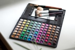 A palette with multi-colored eye shadow and makeup brushes on the windowsill