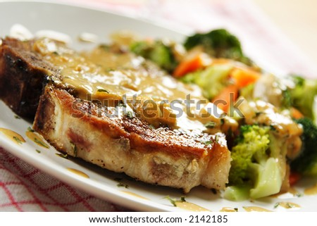A pan fried pork chop with vegetables and coconut sauce - stock photo
