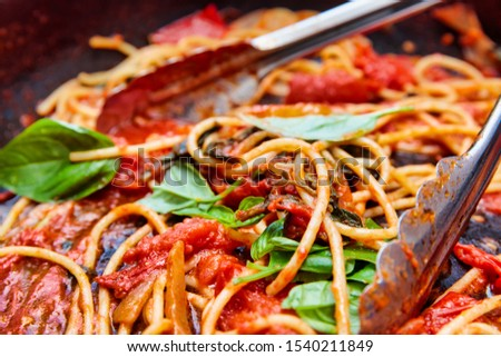 A pan of rustic cooked spaghetti / pasta, sweet tomato sauce and basil leaves.