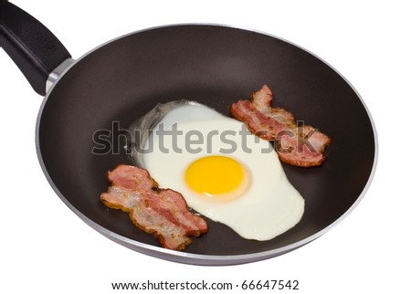 A pan with a fried egg and two pieces of bacon isolated