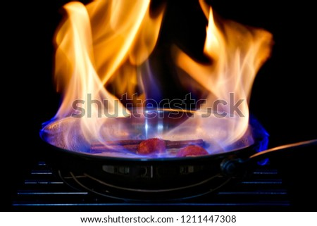 A pan with flames flambeing fruit. Black background. Stock photo ©