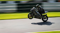 A panning shot of a grey racing bike on one wheel as it circuits a track