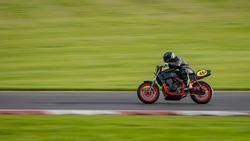 A panning shot of a racing motorbike as it circuits a track.