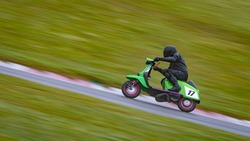 A panning shot of a racing scooter as it circuits a track.