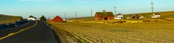 A panorama image of a wheat farm with three red barns on Despain road near Pendleton, Oregon