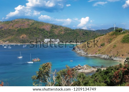 a panorama landscape wallpaper of a turquoise water bay surrounded by colorful trees, hills and mountains, blue sky and white clouds on background. Taken during vacation on Phuket island, Thailand #1209134749