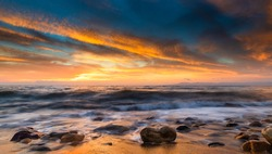 A Panorama Of A Colorful Ocean Sunset Sky As A With As A Gentle Wave Rolls In Among The Seashore beach Rocks And Sand