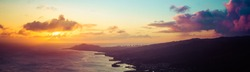 A panorama of a sunset over the Hawaiian Island of Oahu as seen from a mountain top with the city of Waikiki Beach and Diamond Head in the distance.  Image captured from the summit of Koko Head Crater