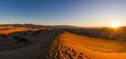 A Panorama of sand dunes in Death Valley near stovepipe wells during sunrise in Death Valley National Park.