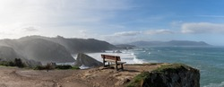 A panorama of scenic viewpoint with wooden bench on beautiful ocean coast with high cliffs and big waves