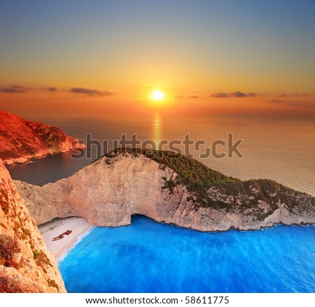 A panorama of sunset over Zakynthos island, Greece with a shipwreck on the sandy beach