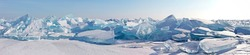 A panorama of the edge of a hummock field with beautiful huge blocks of transparent blue ice on the frozen Lake Baikal on a sunny frosty day. Cool natural background. Unusual winter landscape