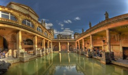 A panorama of The Roman Baths in Bath, England on a bright, sunny day.