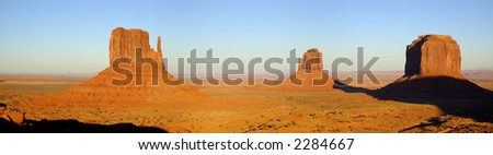A panorama shot of West Mitten, Last Mitten and Merrick Buttes lit by the sunset sun in Monument Valley (Navajo Nation).