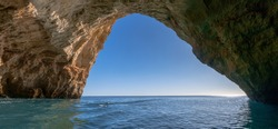 A panorama view from inside a cave on the ocean coast with turquoise water and sunny blue sky outside