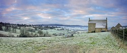 A panorama view of a cold and frosty sunrise over an isolated farm house and a distant view of the Cotswold village of Painswick, Gloucestershire, England, UK