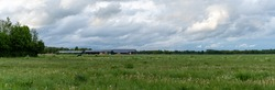 A panorama view of typical large Dutch farm with many buildings and fields under an overcast sky