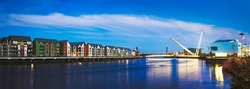 A panoramic of Newport City's riverfront along the river Usk with the Millennium footbridge and riverside residential buildings, bridges and theaters.
