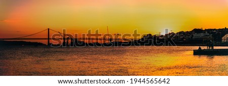 A panoramic shot of a dramatic sunset on the Tagus river with silhouettes of a suspension bridge '25 of Abril' in the background, orange reflections of the sun in the water, houses, and cranes Foto stock ©
