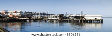 A panoramic shot of an old run down building on a pier in the pacific northwest.