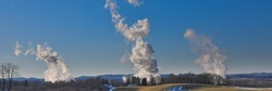 A panoramic shot of smokestack emissions from coal-fired powerplants photographed against a rural West Virginia backdrop under a clear blue sky
