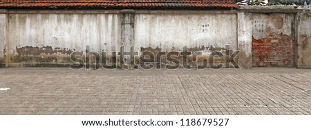 A panoramic stretch of old masonry wall along a cobble stone sidewalk.
