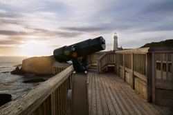 A panoramic tourist's telescope, on a wooden observation walkway, overlooking the Pacific Ocean with Yaquina Head Lighthouse in the background