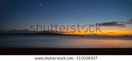 A panoramic view of a new day as the sun rises behind Rangitoto Island, Auckland, New Zealand