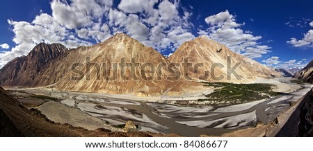 A panoramic view of Kashmir Valley, yellow colored mountains and small village at the base of mountains;  Kashmir, India