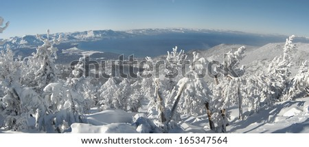 A panoramic view of Lake Tahoe on a very cold sunny winter day after a big snowstorm, shot from one of the mountain tops. Deep snow covers the land, pines and surrounding snowcapped mountains.