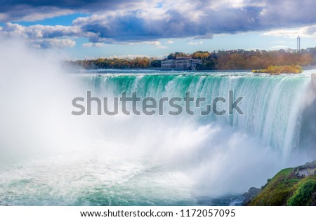 A panoramic view of Niagara falls up close. The dark clouds hovering around & the following foliage, in the distance mage this pic even more special.