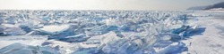 A panoramic view of the endless field of ice hummocks. Pieces of blue transparent ice on the frozen Lake Baikal on a frosty winter day. Natural cold background. Unusual winter landscape