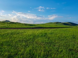 A panoramic view on a hilly landscape of Xilinhot in Inner Mongolia. Endless grassland with a few wildflowers between. Blue sky with thick, white clouds. Higher hills in the back. Mongolian grassland