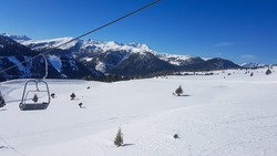 A panoramic view on the snow covered slopes of Innerkrems, Austria. The slopes are ready for skiing. Cloudless, blue sky. Many Alpine chains in the back. Winter wonderland. Ski lift on the side