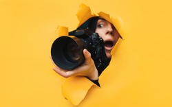 A paparazzi girl with a black reflex camera looks out from cover and looks at what is happening with her mouth open. Yellow paper, torn hole. Tabloid press. In search of the plot for photo stocks.