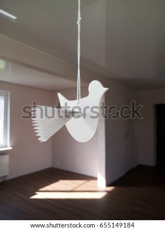 A paper bird. It hangs on a string. Hanging from the ceiling #655149184
