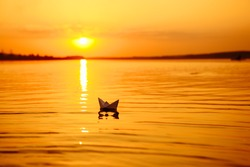 A paper boat floating away into the distance. Boat on the water. Beautiful sunset. Origami. River. Lake.