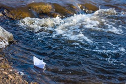 A paper boat on a turbulent stream of water struggles with the flow. Small paper boat is flowing along river.