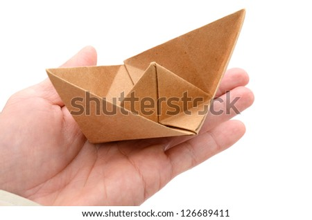 A paper boat on holding hand - stock photo
