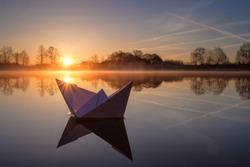 A paper boat sailing along the river at dawn.