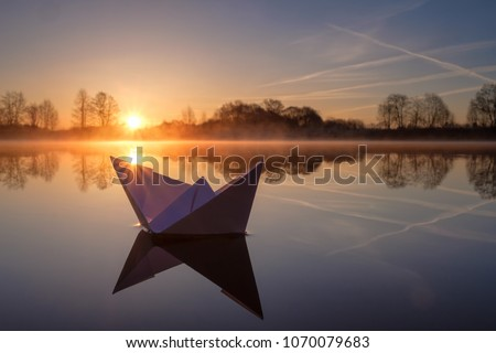 A paper boat sailing along the river at dawn. #1070079683