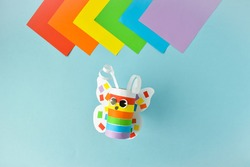 A paper butterfly made of colored paper. Step-by-step instructions for LGBT characters. Step 3. Glue and twist. The butterfly is ready.