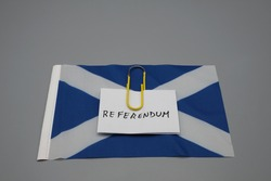 A paper clip with a note, written , referendum, on top of a flag of a Scotland. Popular consultation concept