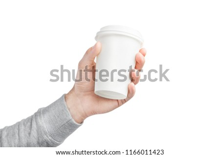 A paper cup of coffee in the hand. White paper cup of coffee in hand. For mock up/ Isolated #1166011423