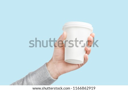 A paper cup of coffee in the hand. White paper cup of coffee in hand. For mock up. Isolated #1166862919