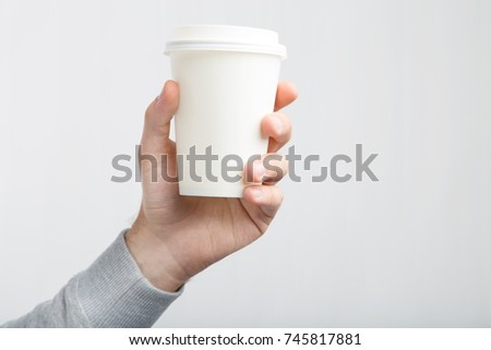 A paper cup of coffee in the hand. White paper cup of coffee in hand. For mock up/ Isolated #745817881