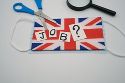 A paper inscription, job, with a question mark, cut by scissors,above a flag of Great Britain and a face mask, with magnifying glass nearby. Concept of employment crisis due to the virus