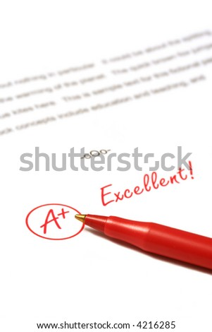 A paper is graded A Plus, Excellent, with red pen.